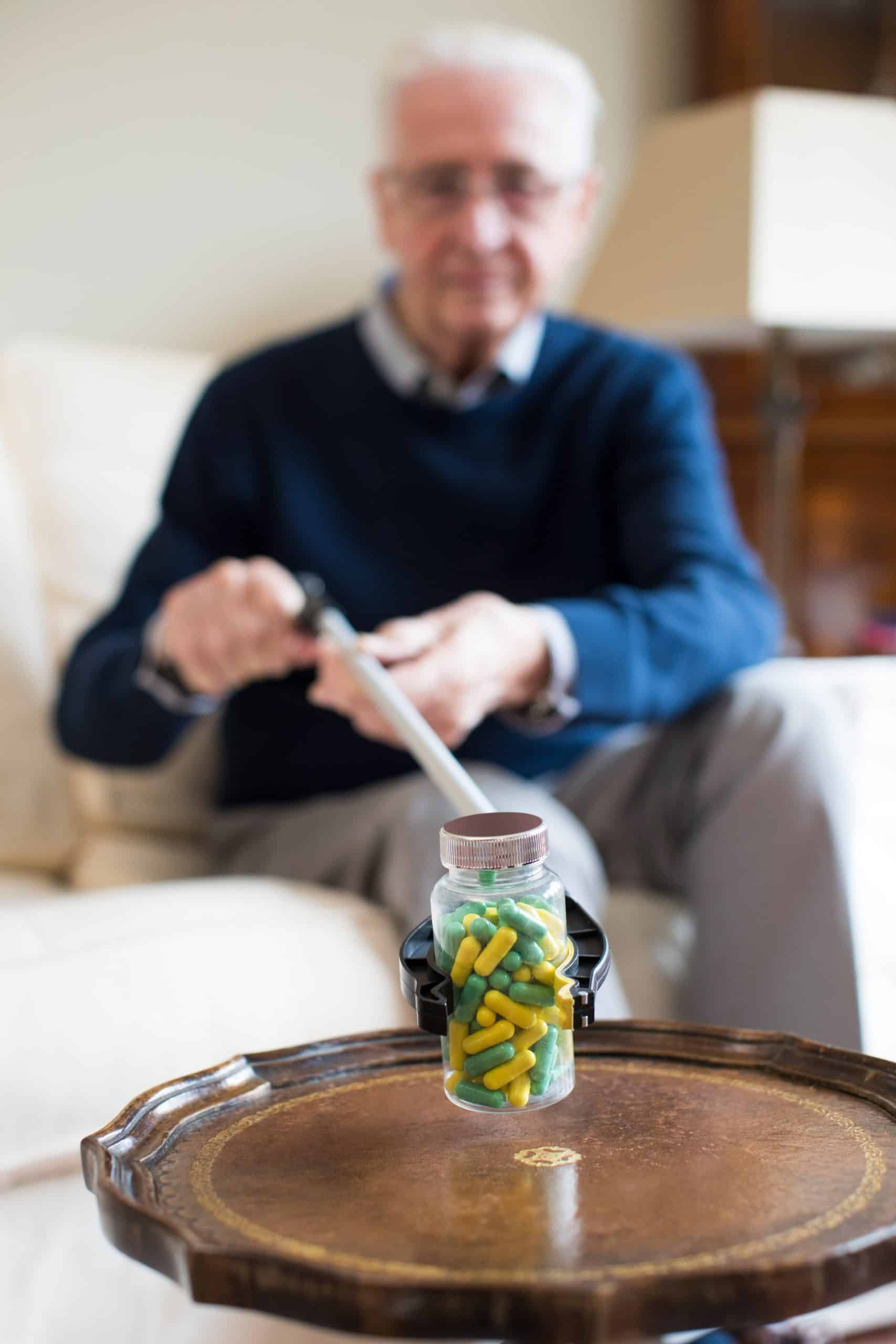 Senior Man Using Reaching Arm To Pick Up Medication At Home