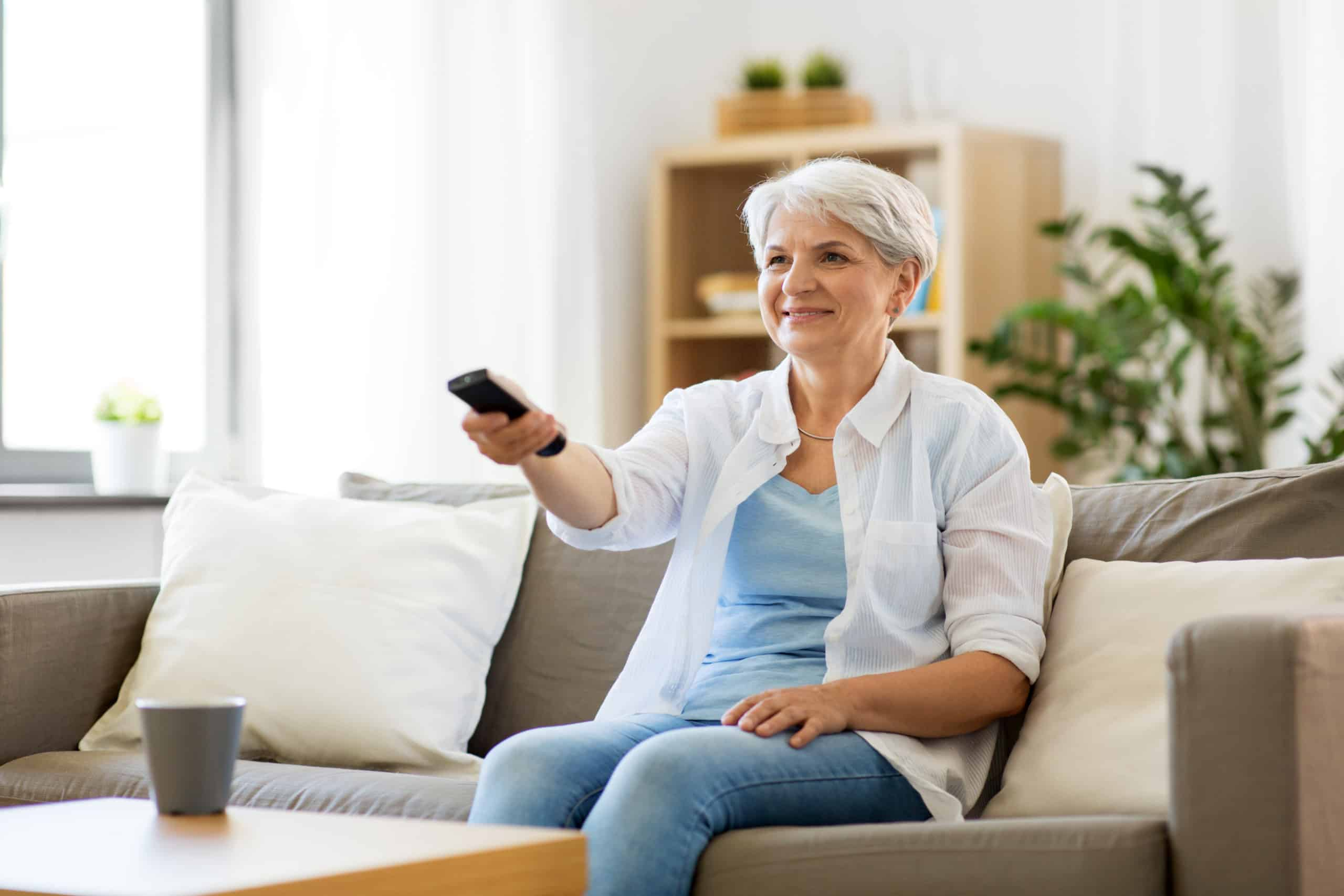 senior woman in eyeglasses with remote control watching tv at home