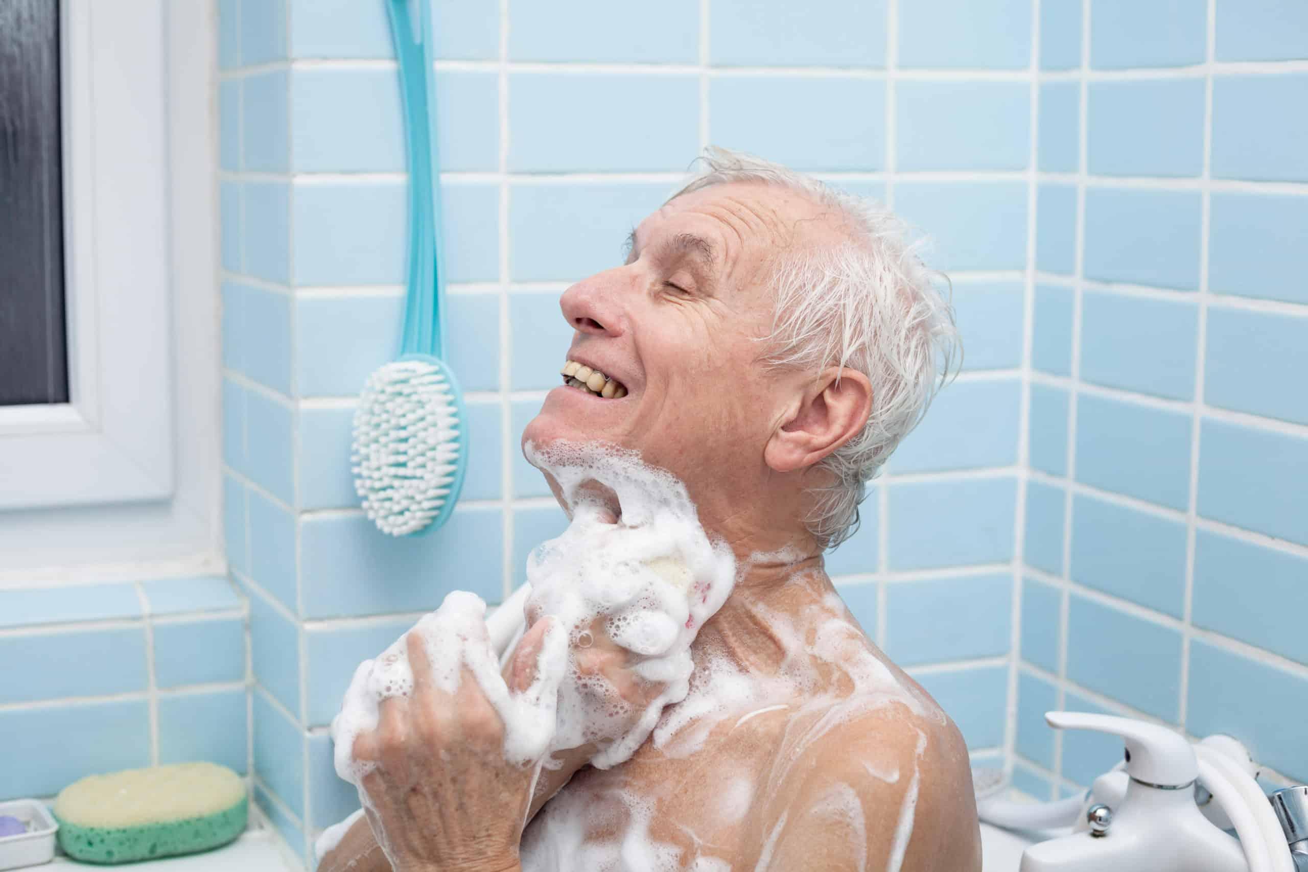 Senior man washing his body with soap in bath.