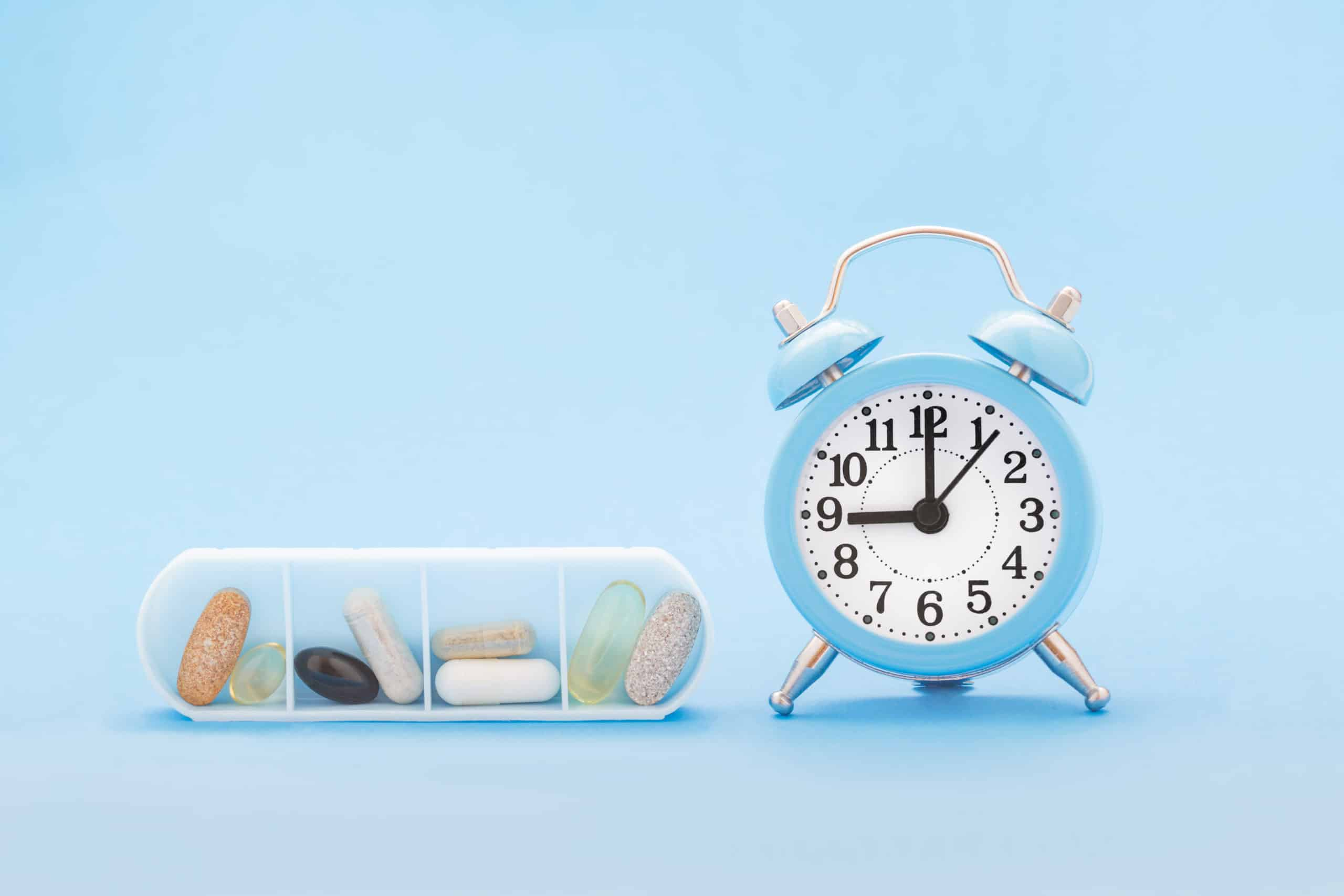 Various pills and capsules in organizer and clock on blue background.