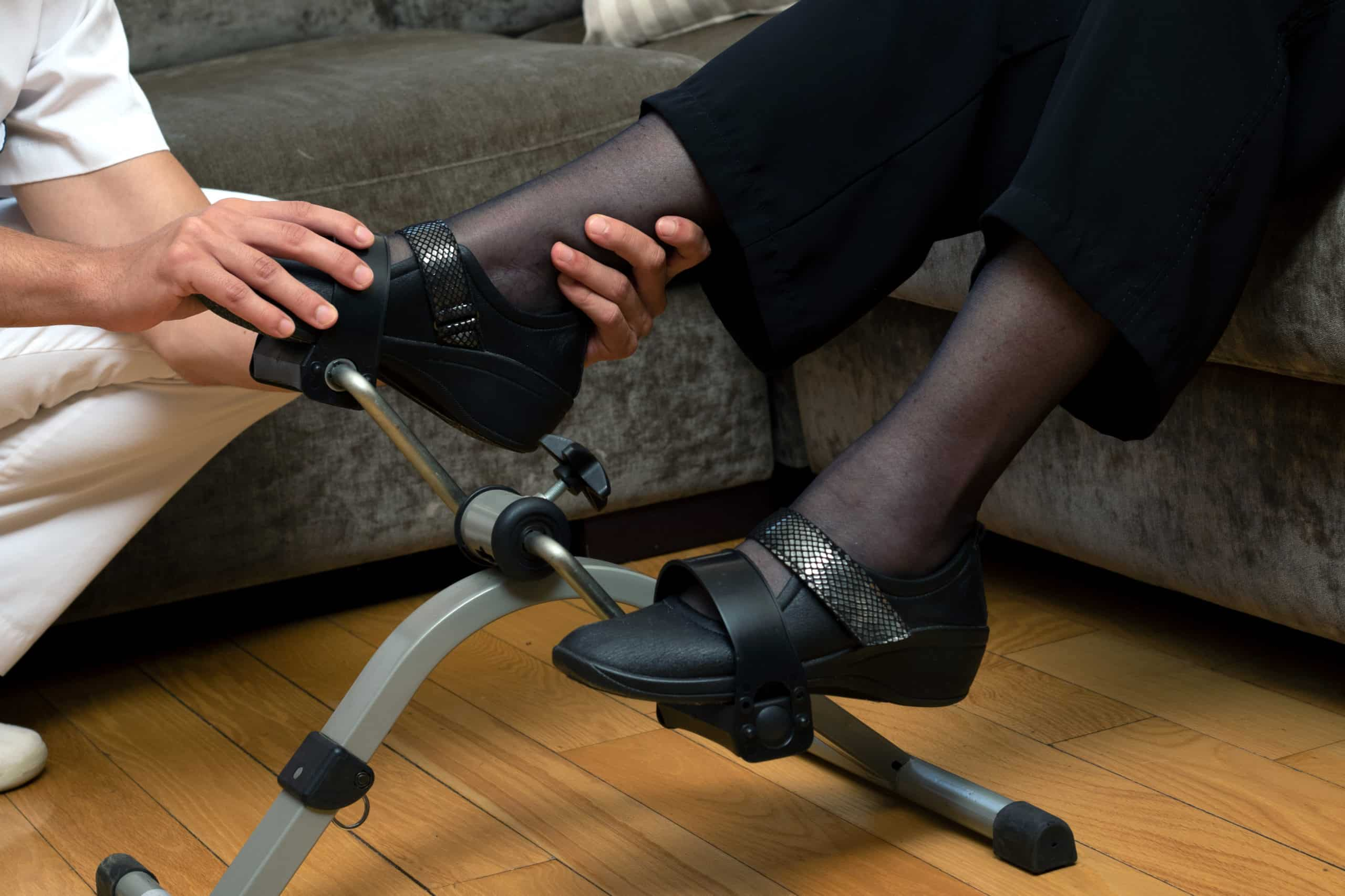 male therapist assisting senior woman's foot in stationary rehabilitation pedals.