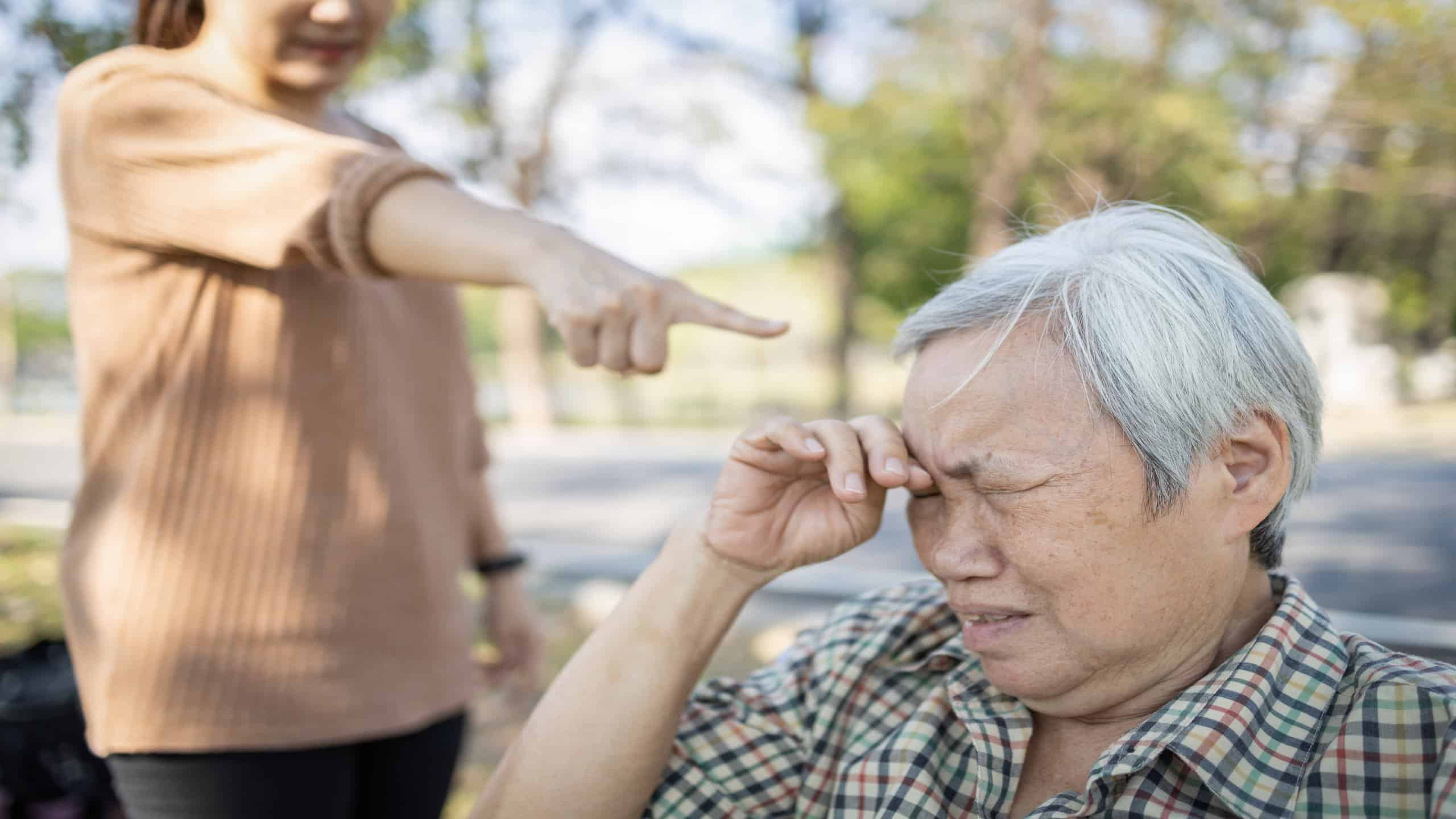 Asian elderly people crying while young caregiver scolding,angry annoyed woman getting mad pointing finger to senior woma