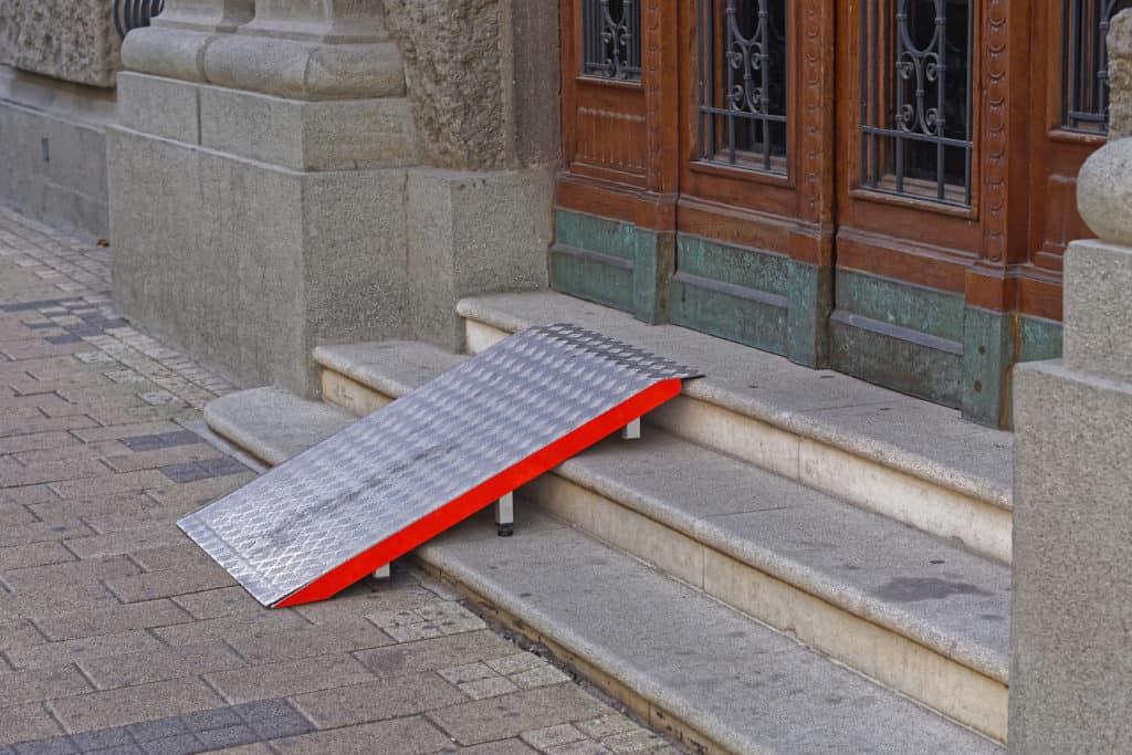 Wheelchair ramp at old building entrance stairs