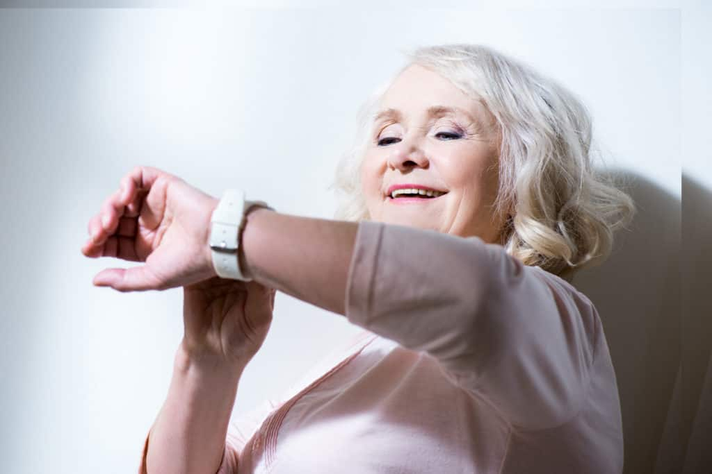 Happy beautiful senior woman checking smartwatch isolated on white